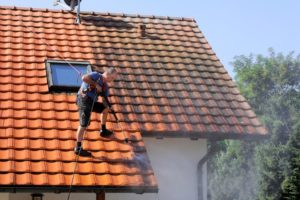 Man pressure washing a roof.