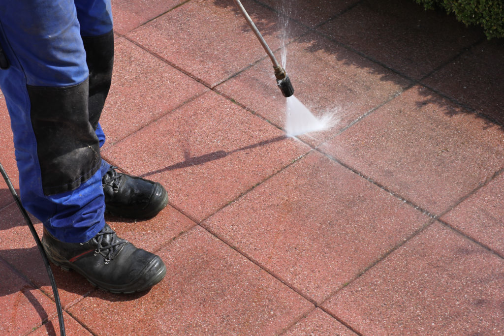 A pressure washing technician cleans a pathway.